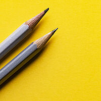 two grey led pencils sitting on a yellow background