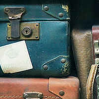 pile of old fashioned leather suitcase with travel stamps on them