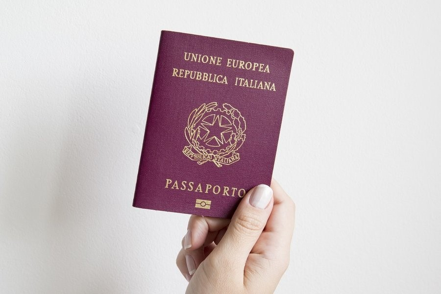 person holding Italian passport