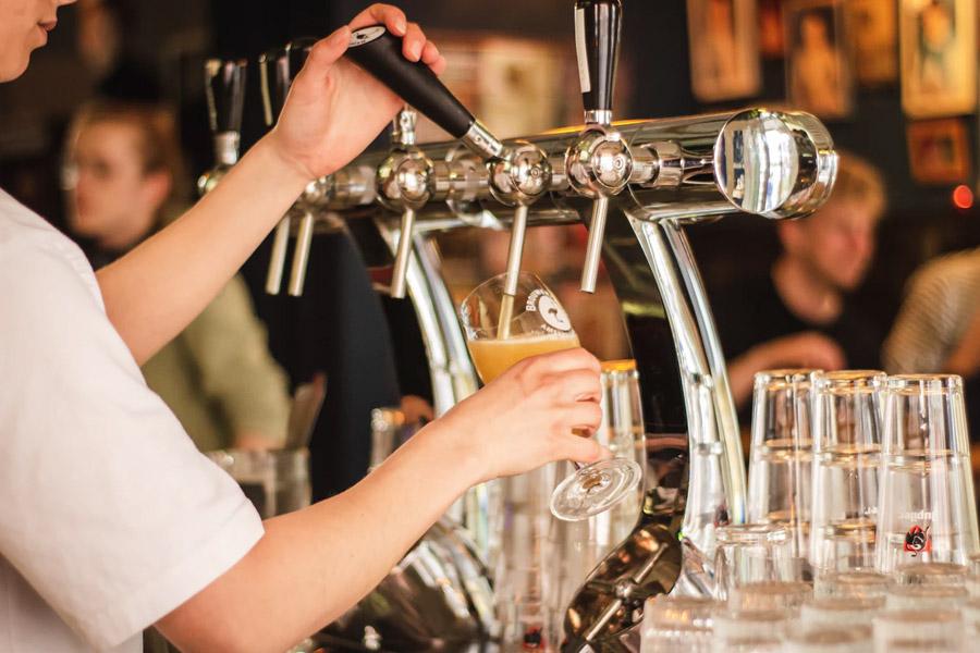 Man pulling a pint at a bar