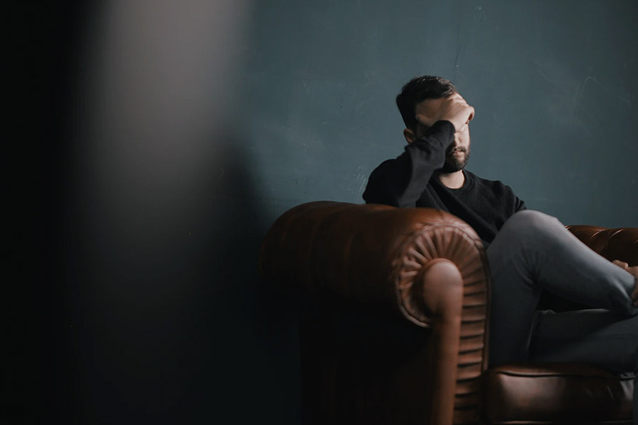 man on a sofa holding head in hand looking depressed