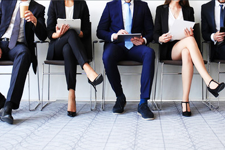 a row of people in office clothing sitting down in a line