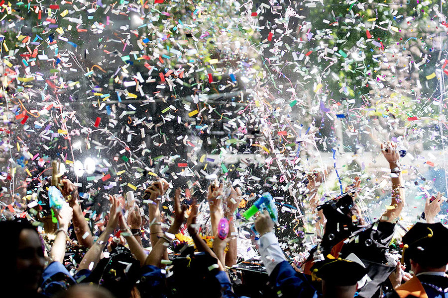 group of graduated students celebrating with confetti falling