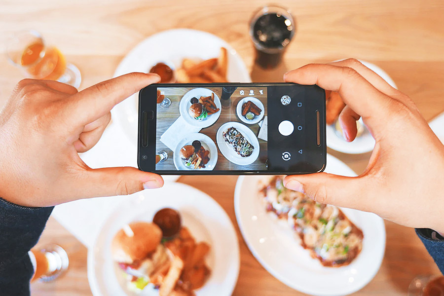 person taking a picture of a range of food with a smartphone camera