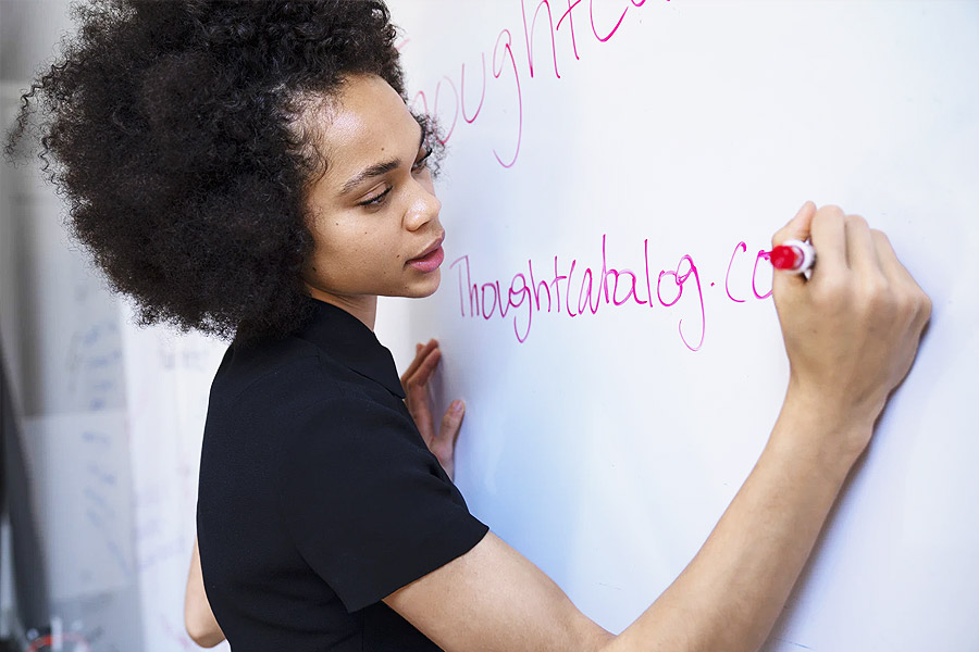 young adult woman writing on a whiteboard