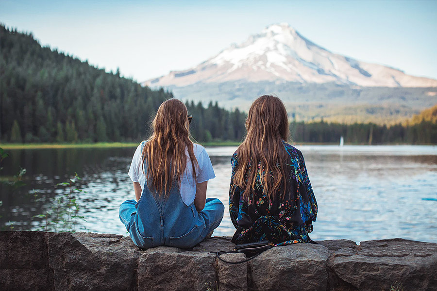 two friends sat together in a mountain scene