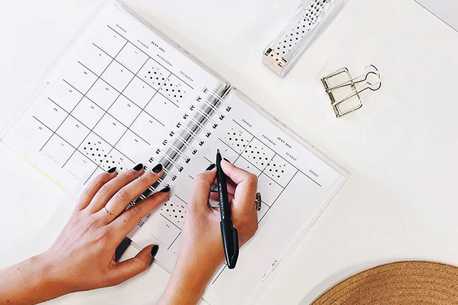 writing on a plan in a calendar on a white desk