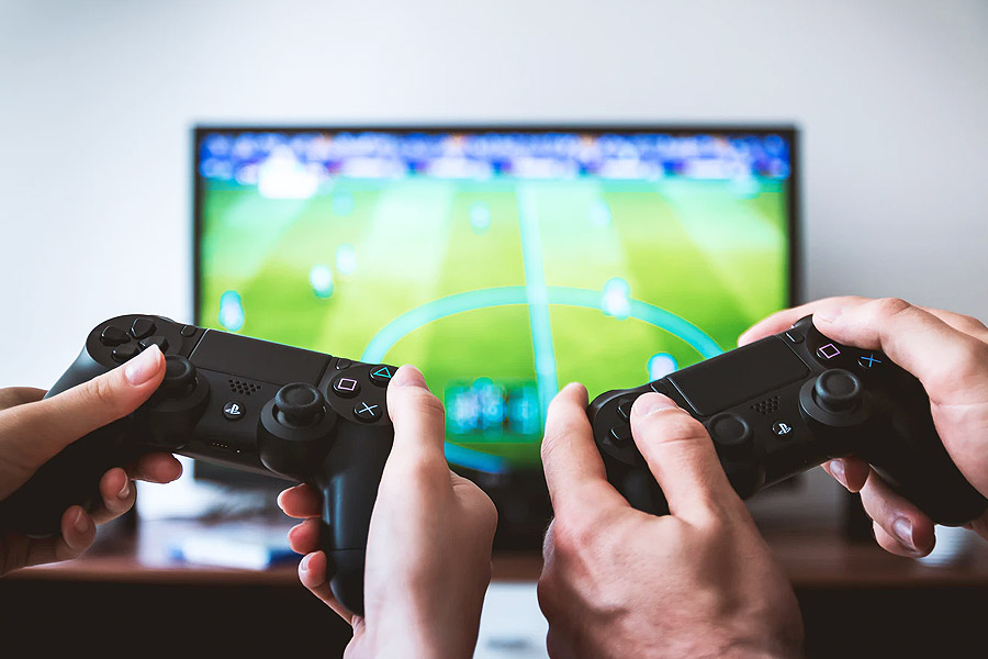 two game controllers with TV in the background playing a football game