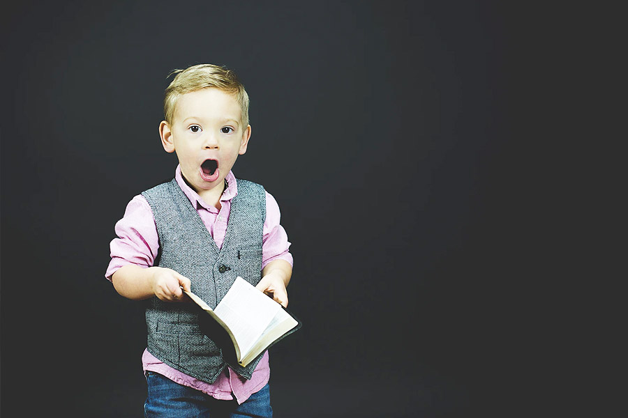 young boy on a grey background looking shocked reading a book