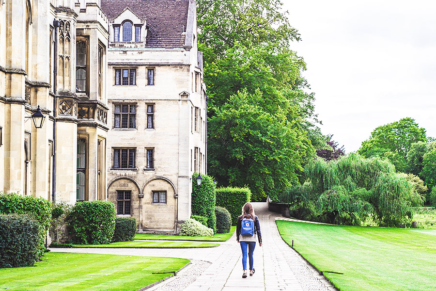 young adult with back pack walking next to old university building
