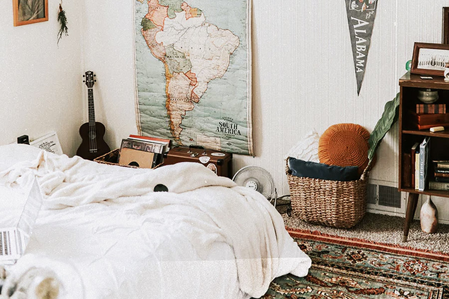 a young adult room furnished with travelling goods and a guitar