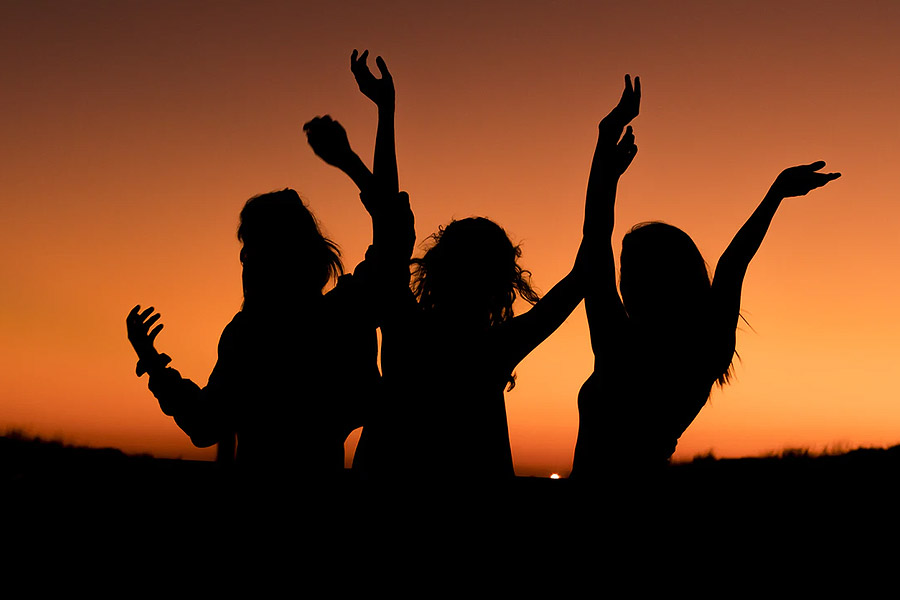 three ladies dancing silhouette in a sunset