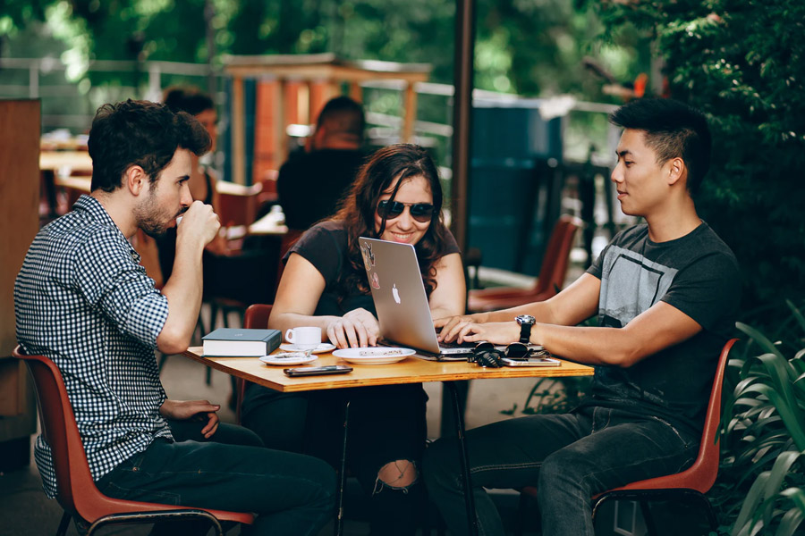 group of friends with laptop studying in a cafe