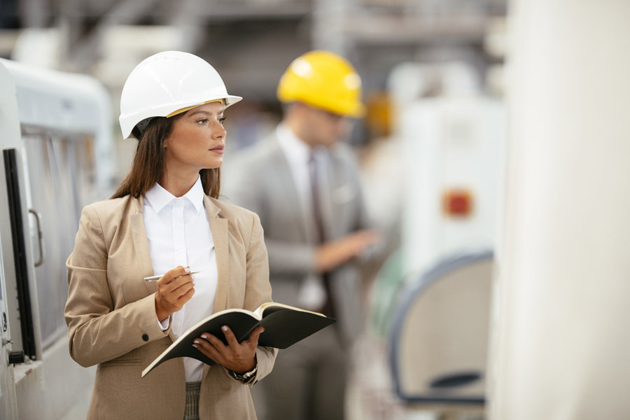 woman in a suit and hardhat holding a clipboard